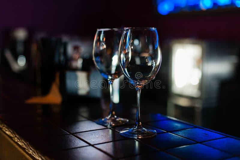 Tomma vinexponeringsglas i rad på stång eller restaurang royaltyfri foto