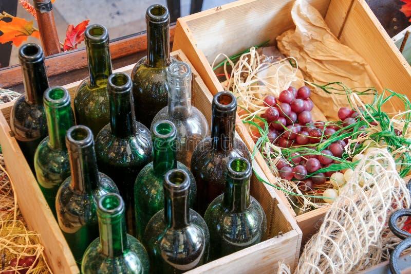 Tomma vinflaskor i en träask och druvor royaltyfria bilder
