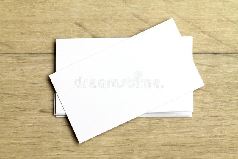 Tomma vita affärskort på en ljus träbakgrund Modell för att brännmärka identitet arkivfoton