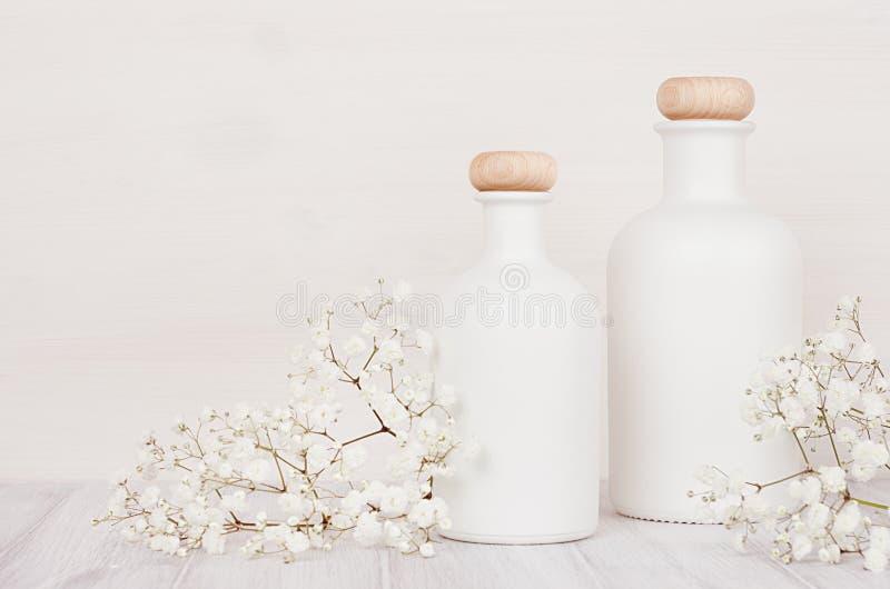 Tomma vita skönhetsmedelflaskor med små blommor på det vita wood brädet, förlöjligar upp royaltyfri foto