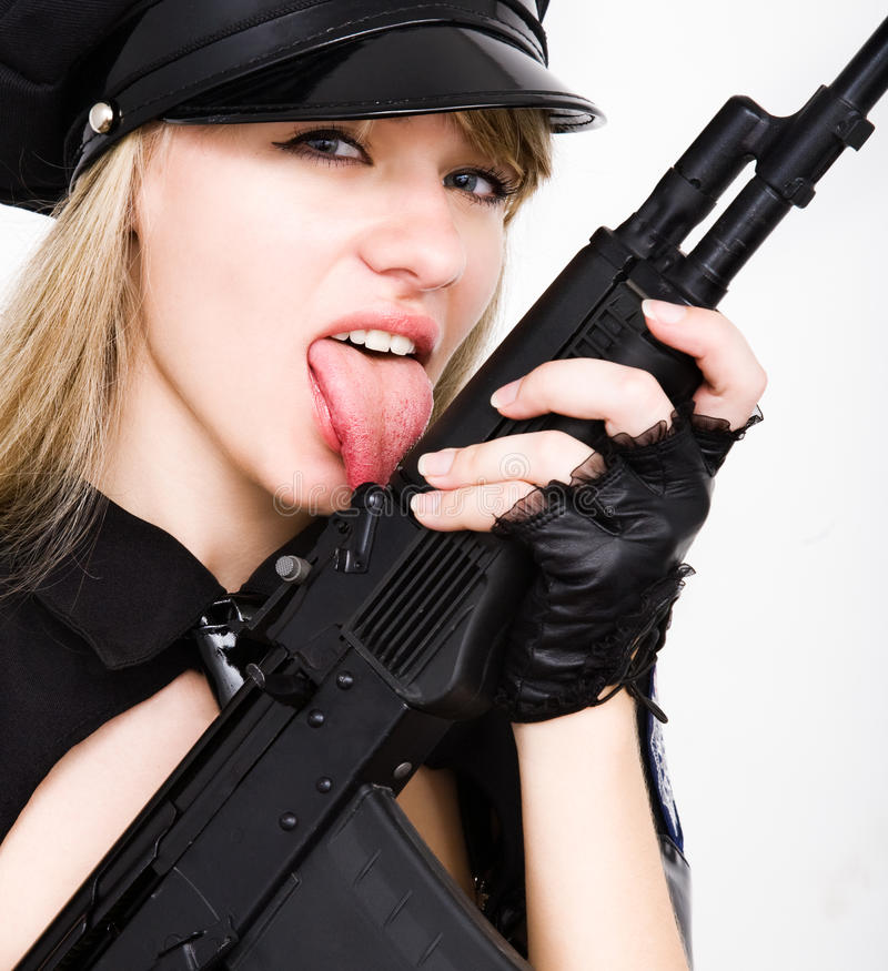 Tommy gun. Portrait of young woman licking with tongue black tommy gun stock photos