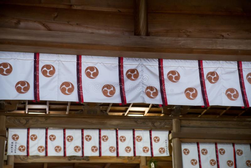Tomoe banners at Shinto shrine, Nobeoka, Japan. WIde angle detail of multiple cloth banners with triple tomoe symbols on the wooden strut ceiling of a Shinto stock photos