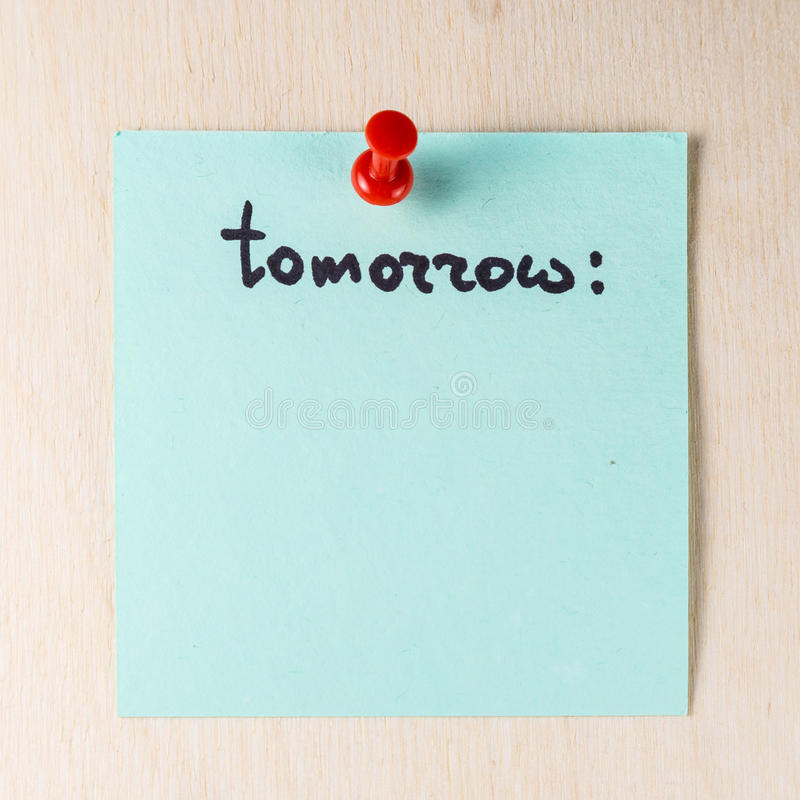 Tomorrow note on paper post it. Pinned to a wooden board stock photography