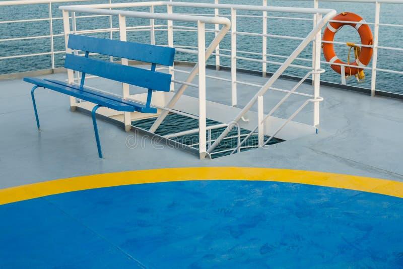 Tomt övredäck med den blåa träbänken och helikopteruppsamlingspunkt på den grekiska färjan royaltyfria foton