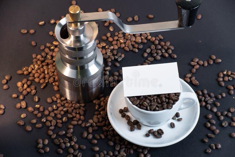 Tomt affärskort i kopp och kaffekvarn för vitt kaffe i kaffebönor royaltyfria bilder