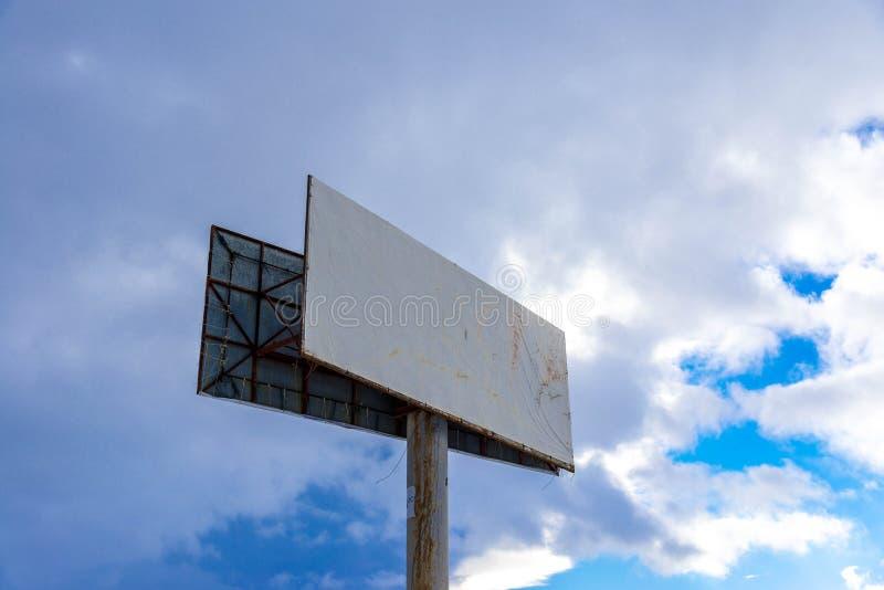 Tomt affischtavlatecken mot stormmoln på blå himmel royaltyfri foto