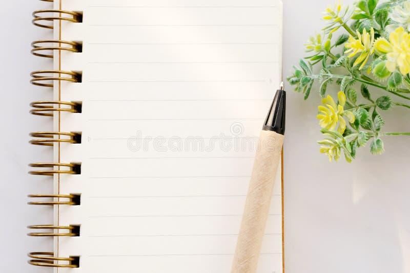 Tomt anteckningsbokpapper och penna på vit marmorbakgrund, med kopieringsutrymme för text, bästa sikt royaltyfri fotografi