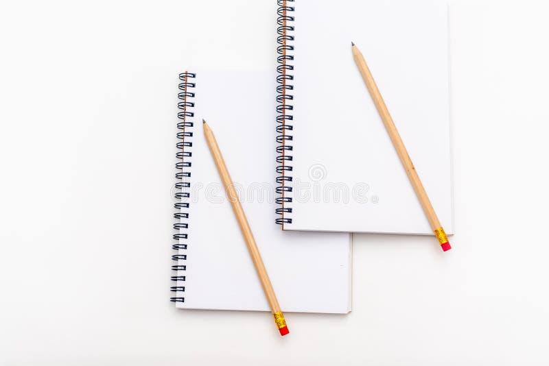 Tomt ark av anteckningsboken med en spiral och pennan p? en vit bakgrund kopiera avst?nd royaltyfri bild