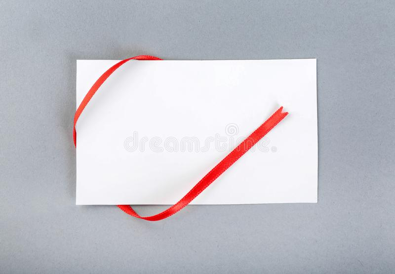Tomt ark av papper med det röda bandet på grå bakgrund arkivbild