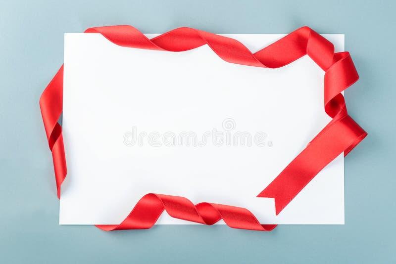 Tomt ark av papper med det röda bandet på grå bakgrund royaltyfri fotografi