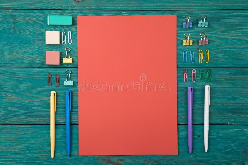 Tomt ark av papper och färgrik kontorstillbehör royaltyfri fotografi