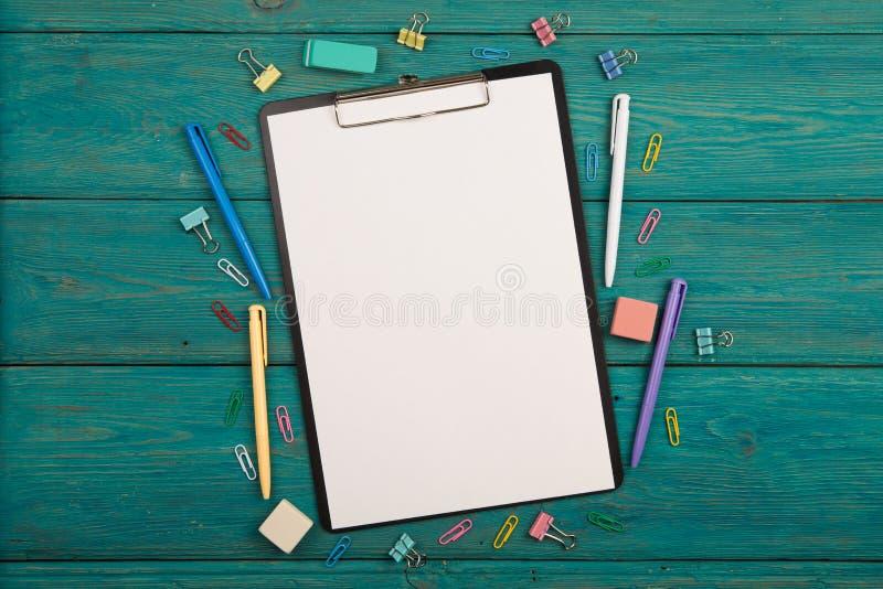 Tomt ark av papper och färgrik kontorstillbehör royaltyfria foton