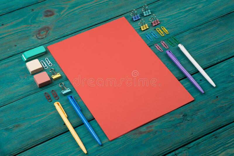 Tomt ark av papper och färgrik kontorstillbehör royaltyfri foto