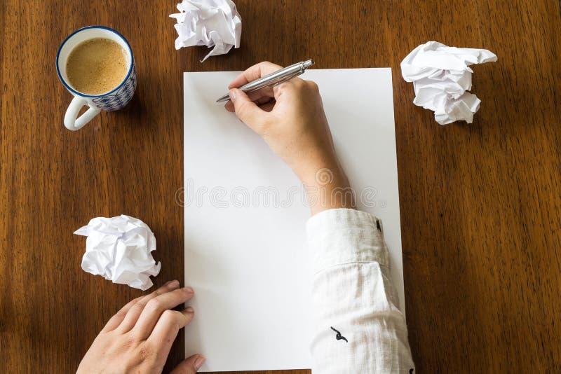Tomt ark av papper och pennan på det ljusa träkontorsskrivbordet med händer av en person arkivbild