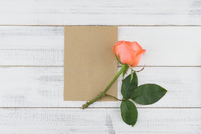 Tomt brunt kort med apelsinrosen på vit wood bakgrund royaltyfria bilder