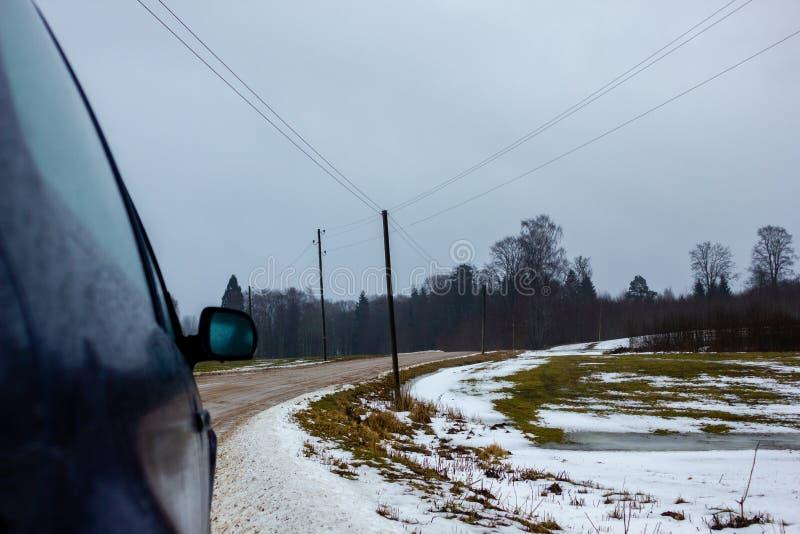 Tomt bygdlandskap i molnig vinterdag med snö som täcker delvis jordningen och dimman - del av bilen i förgrunden arkivfoto