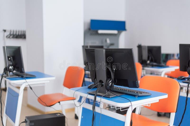 Tomt datorklassrum med ljusa bl?a skrivbord och orange stolar undervisande barn programmera arkivfoton