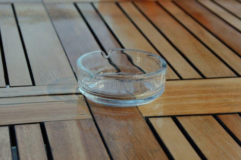 Tomt exponeringsglasaskfat av rund form på en trätabell royaltyfri fotografi