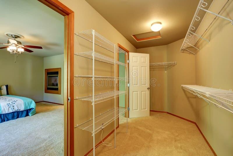 Tomt gå till och med garderoben med hyllor i sovrummet arkivbilder