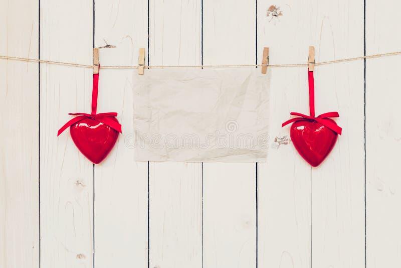 Tomt gammalt papper och röd hjärta som hänger på wood brädebakgrund arkivbild
