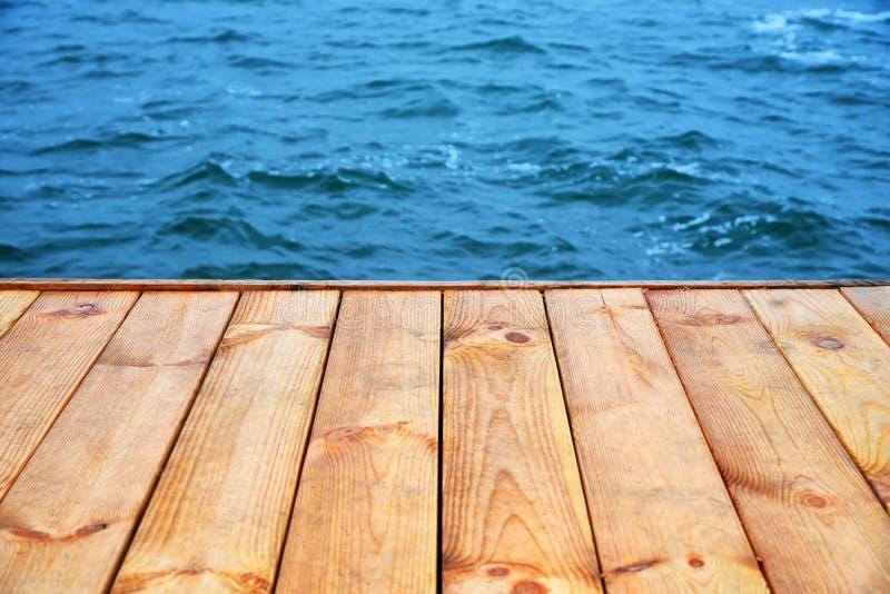 Tomt golv för träbräde framme av havsbakgrund för blått vatten fotografering för bildbyråer