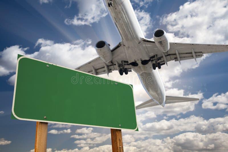 Tomt grönt vägmärke och flygplan över arkivfoto