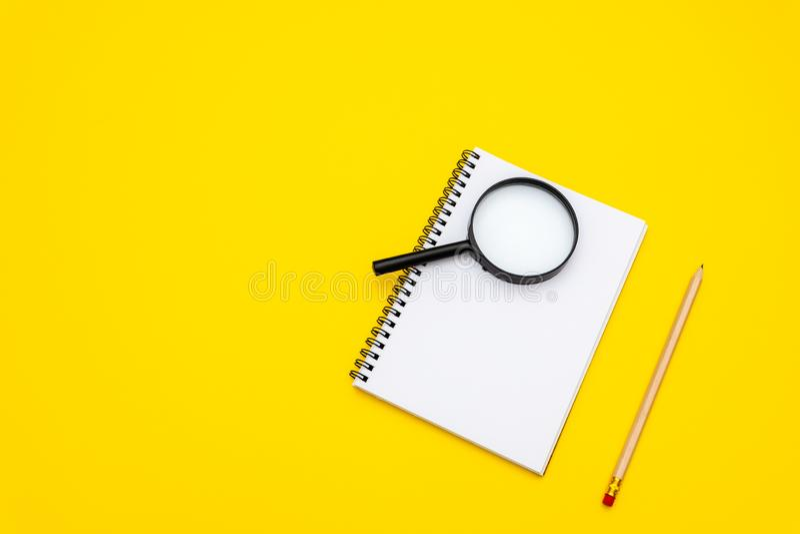 Tomt handstilblock f?r id?er och inspiration p? kul?r bakgrund F?rstoringsglas ?verst av notepaden arkivbilder