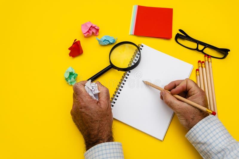 Tomt handstilblock f?r id?er och inspiration p? kul?r bakgrund F?rstoringsglas ?verst av notepaden B?sta sikt p? att skriva m?n arkivfoto