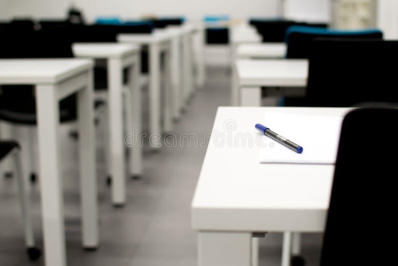 Tomt klassrum H?gstadium eller universitetskrivbord eller tabell med en penna ?verst royaltyfri foto
