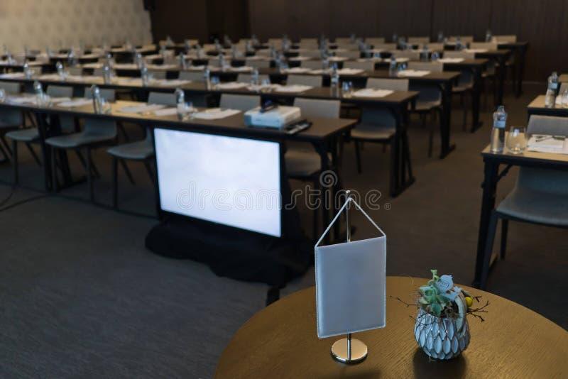 Tomt konferensrum, vit flagga i förgrund, bildskärm, stolar och tabeller arkivbilder