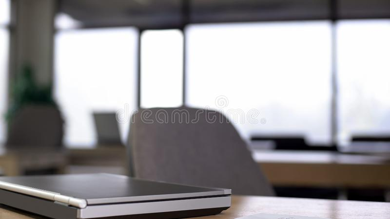 Tomt kontor, bärbar dator som ligger på tabellen, slut av arbetsdags, modern utrymmeinre royaltyfri foto
