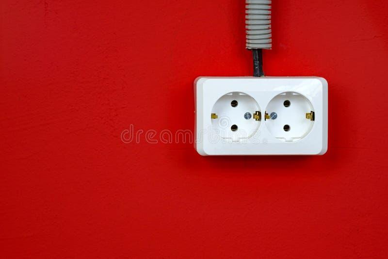 Tomt kopplat från europeiskt slut för vägguttag upp på röd bakgrund Vit elektrisk h?lighet p? den r?da v?ggen closeup arkivfoton