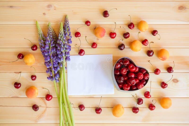Tomt kort för dina text, blåa vildblommor lupine, ask för hjärtaformgåva med nya körsbärsröda och nya frukter omkring royaltyfria bilder