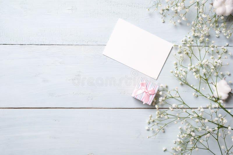 Tomt kort för inbjudan eller lyckönskan, liten gåvaask, grupp av gypsophilablommor på ljust - blå trätabell Banermocku royaltyfri foto