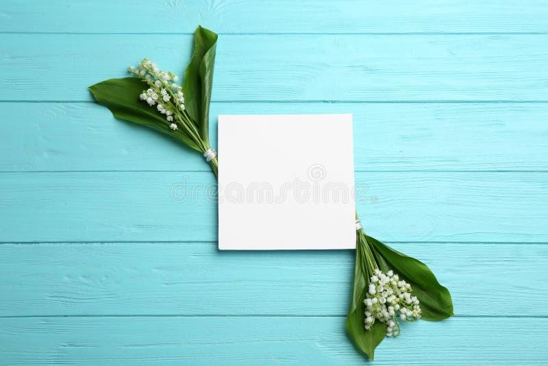 Tomt kort med liljekonvaljbuketter på träbakgrund Utrymme f?r text royaltyfria foton