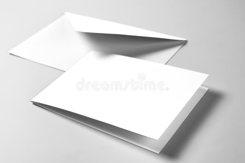 Tomt kort och kuvert över grå bakgrund arkivfoton