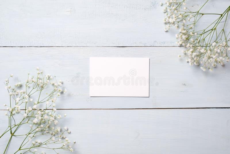 Tomt kort på det blåa träskrivbordet med blommor Tomt hälsa kort för din lyckönskan med den påsk-, moder- eller kvinnas dagen, vå arkivfoto