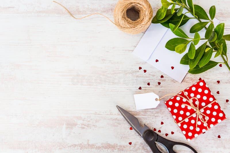 Tomt kort som binds på den röda prickiga gåvaasken över vit wood bakgrund kopiera avstånd Spridd hjärta formade paljetter, ett ku royaltyfri bild