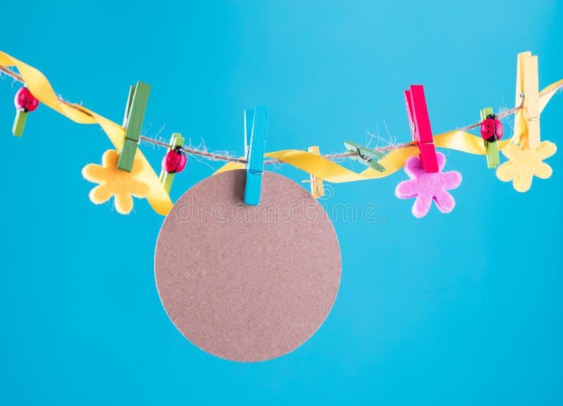 Tomt kort som klämmas fast på klädstreck Kopieringsutrymme för wordings Klämt fast med blommaben Blått orange bakgrund högt royaltyfri foto