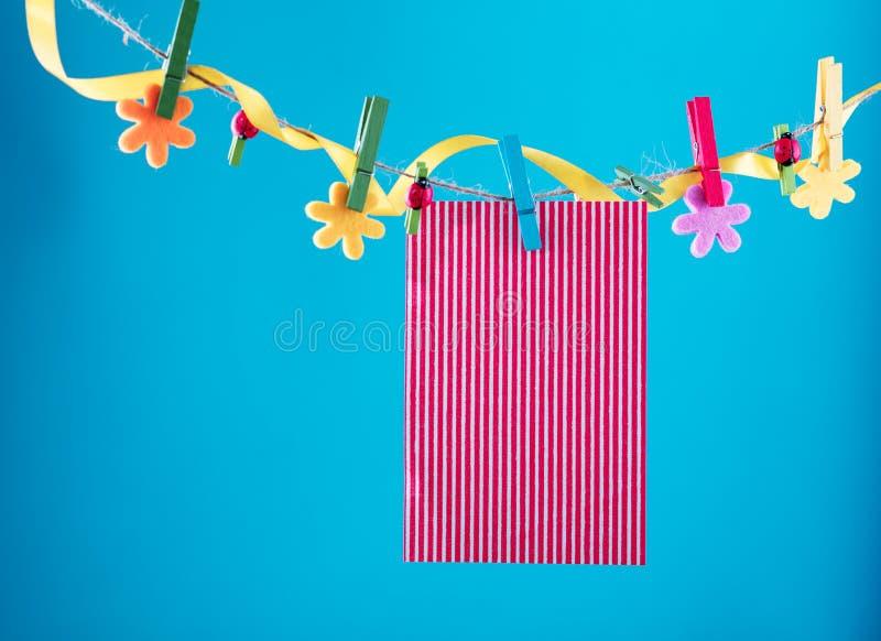 Tomt kort som klämmas fast på klädstreck Kopieringsutrymme för wordings Klämt fast med blommaben Blått orange bakgrund högt arkivfoto