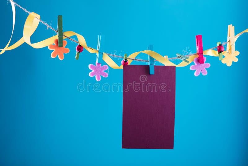 Tomt kort som klämmas fast på klädstreck Kopieringsutrymme för wordings Klämt fast med blommaben Blått orange bakgrund högt fotografering för bildbyråer