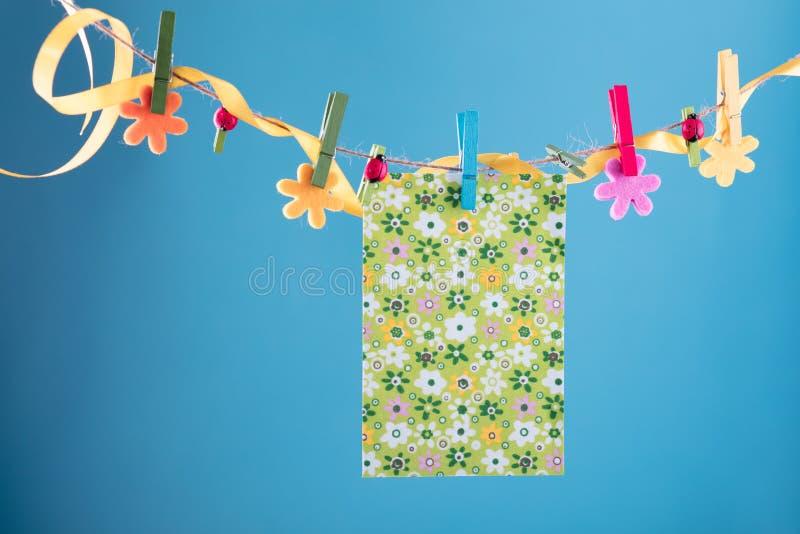 Tomt kort som klämmas fast på klädstreck Kopieringsutrymme för wordings Klämt fast med blommaben Blått orange bakgrund högt arkivbilder