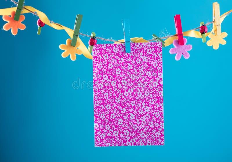 Tomt kort som klämmas fast på klädstreck Kopieringsutrymme för wordings Klämt fast med blommaben Blått orange bakgrund högt arkivfoton