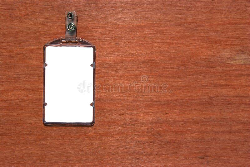 Tomt legitimationkort/emblem på träskrivbordet royaltyfri bild