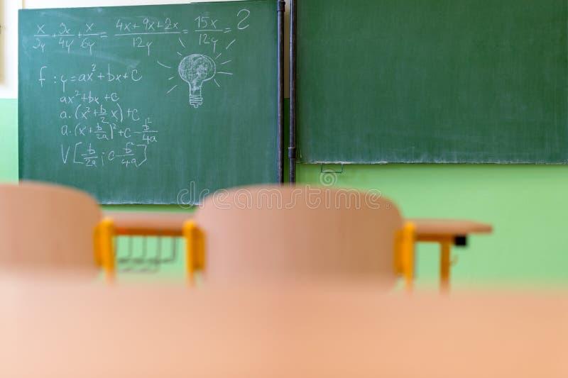 Tomt matematikklassrum med den skolaskrivbord, stolar och svart tavla arkivfoton