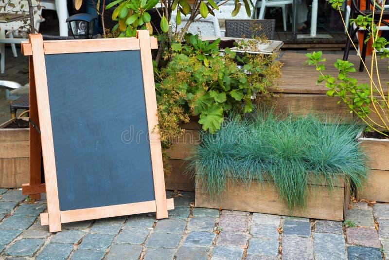 Tomt menyadvertizingbräde och träask av gräs arkivfoto