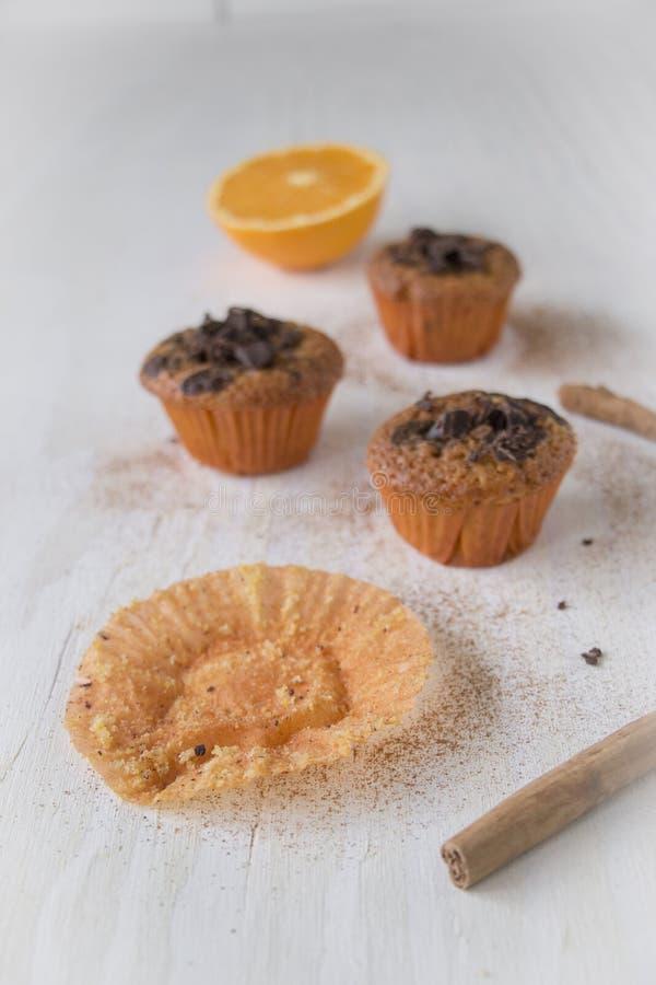 Tomt muffinpappersfall Orange och mörka chokladmuffin med den halva apelsinen i baksidan royaltyfri bild