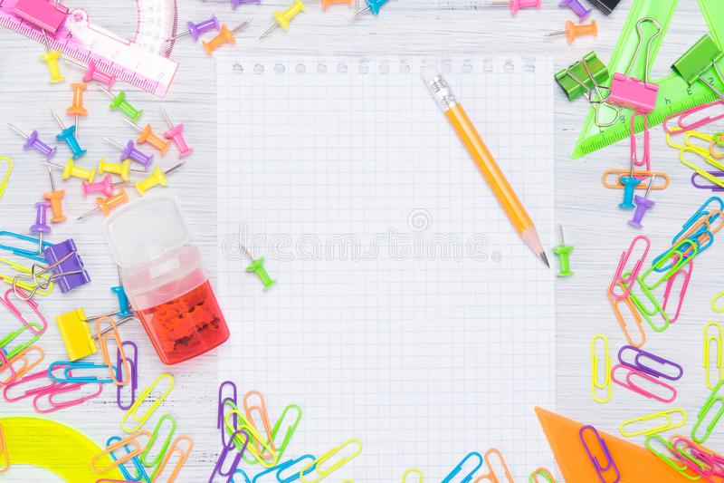 Tomt Notepadark som omges av färgrika kontorstillförsel, gemmar och knappar royaltyfri foto