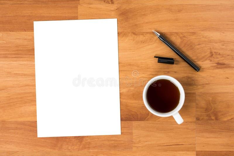 Tomt papper är överst av den wood tabellen med pennan och koppen kaffe, royaltyfria foton