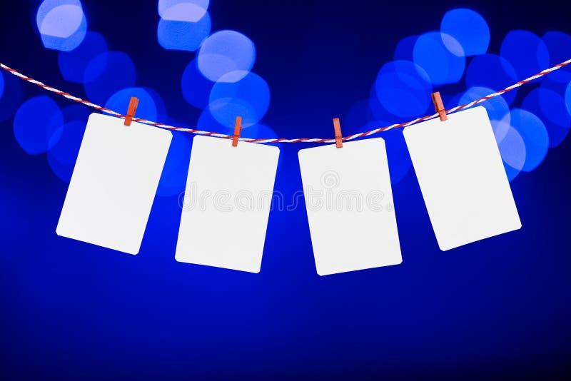 Tomt papper eller fotoet inramar att hänga på det röda randiga repet Suddiga defocused blått färgar ljus bakgrund, mall royaltyfria bilder